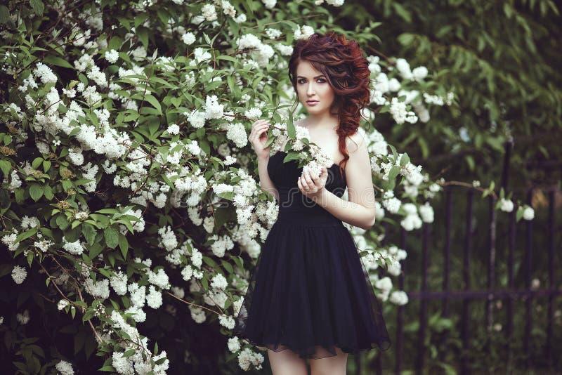Een mooi meisje in een zwarte kleding stelt dichtbij een struik met witte bloemen stock fotografie