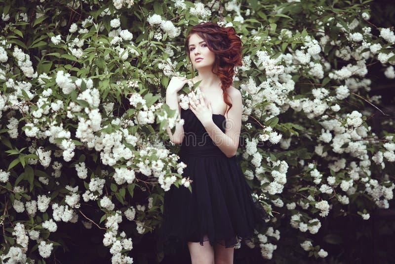 Een mooi meisje in een zwarte kleding stelt dichtbij een struik met witte bloemen royalty-vrije stock fotografie