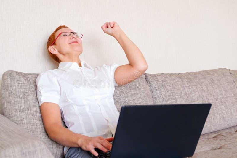 Een mooi meisje in glazen met een rood kader werkt bij laptop Emotie van vreugde met het gebaar van succesvol royalty-vrije stock afbeeldingen