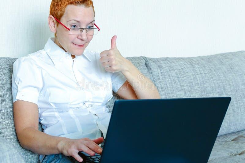 Een mooi meisje in glazen met een rood kader werkt bij laptop Emotie van vreugde met het gebaar van een succesvolle transactie stock foto
