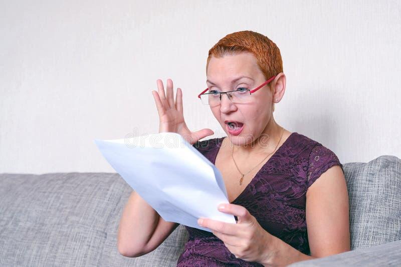 Een mooi meisje in glazen met een rood kader werkt bij laptop Emotie van vreugde met het gebaar van een succesvolle transactie stock afbeelding