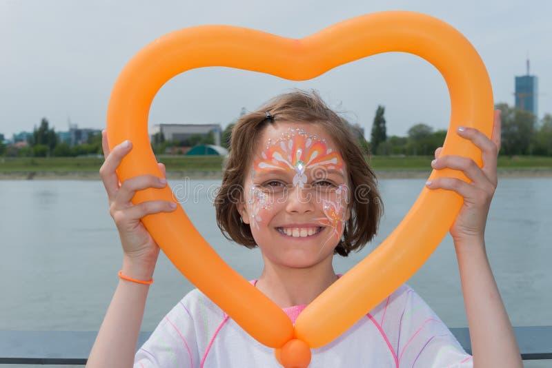 Een mooi meisje heeft een gezicht die en een ballon in vormhart schilderen houden stock afbeelding