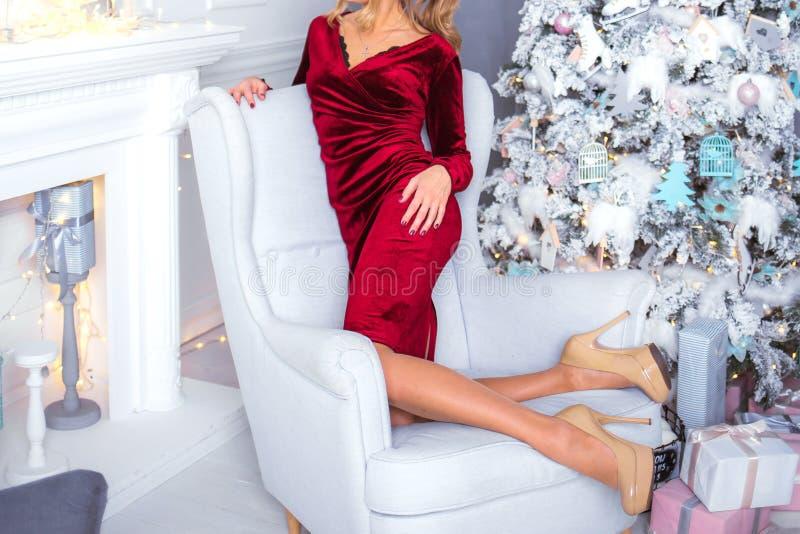 Een mooi meisje in hoge hielenschoenen zit als voorzitter dichtbij CH royalty-vrije stock afbeelding
