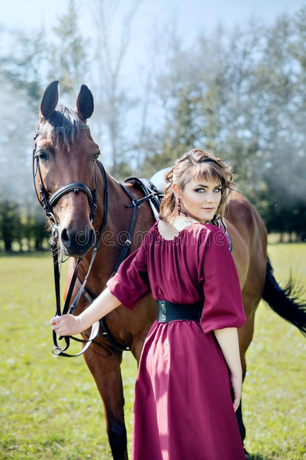 Een mooi meisje in een kleding van Bourgondië houdt een bruin paard stock foto's