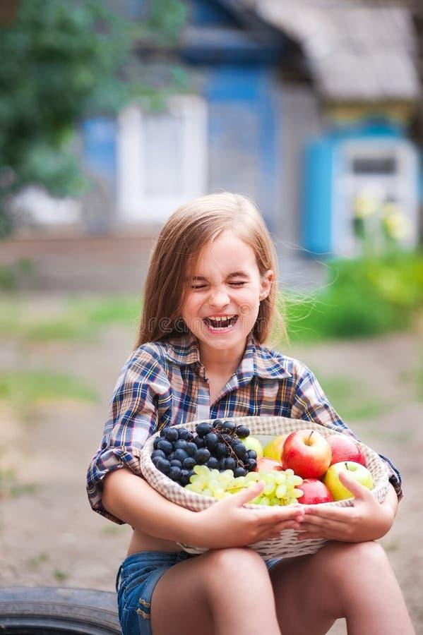 Een mooi meisje lacht met haar gesloten ogen en houdt een mand met de herfstappelen en druiven Een meisje in een plaidoverhemd en royalty-vrije stock foto