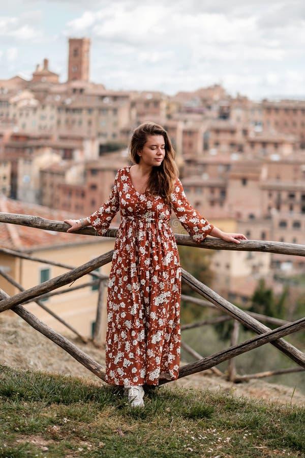 Een mooi meisje in een lange kleding die rond de oude stad van Siena lopen stock afbeelding