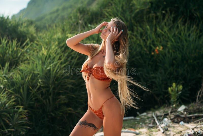 Een mooi meisje met een dunne taille en lange benen, een grote borst rust op het overzees in een modieus zwempak Het model stock foto