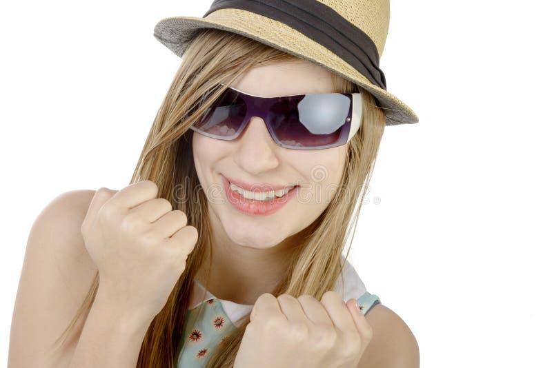Een mooi meisje met een hoed en glazen glimlacht stock foto's