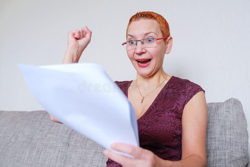 Een mooi meisje met glazen met een rood kader las het positieve nieuws in de documenten Emoties van vreugde met het gebaar van a stock afbeelding