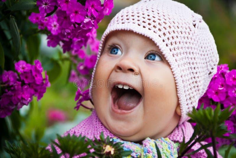 Een mooi meisje met grote blauwe ogen in roze gebreide hoed is gelukkig en lachend onder de rode bloemen in de tuin royalty-vrije stock fotografie