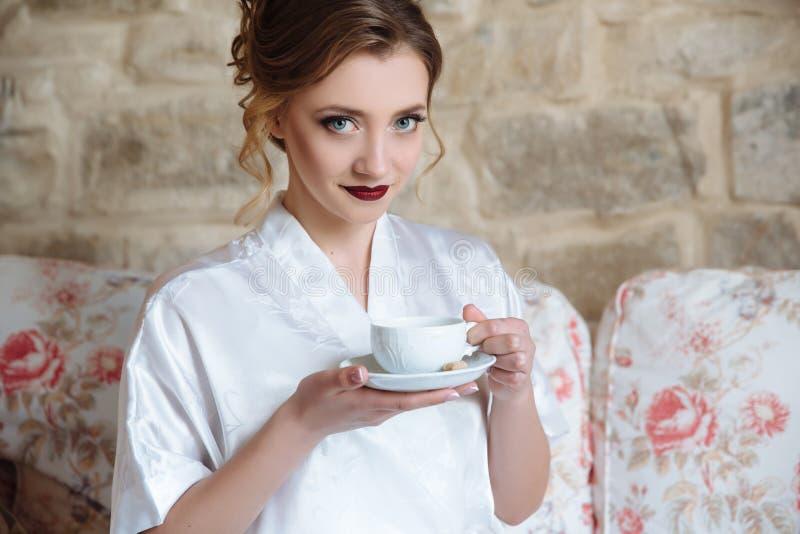 Een mooi meisje met een heldere samenstelling heeft ontbijt en drinkt haar ochtendkoffie Een model met grijs-blauwe ogen royalty-vrije stock foto