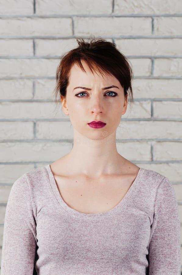 Een mooi meisje met een het fronsen gezicht, grote blauwe ogen, volledige roze lip stock afbeeldingen