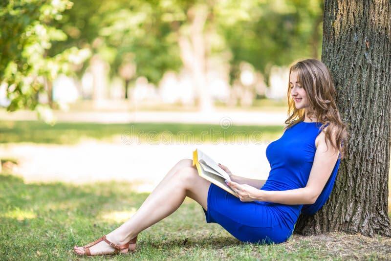 Een mooi meisje met prachtig lichtbruin haar zit dichtbij een grote boom en leest een interessant boek in het groene park royalty-vrije stock afbeeldingen