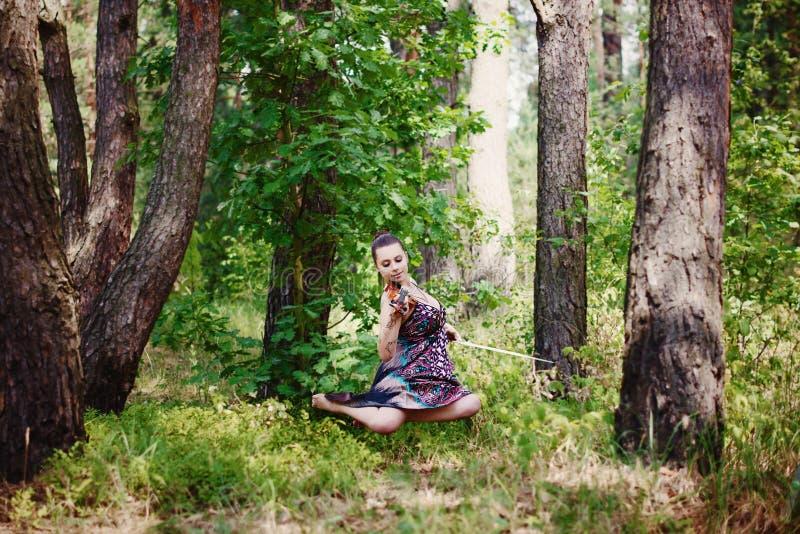 Een mooi meisje met een viool in een lange kleding hangt onder de bomen royalty-vrije stock foto's