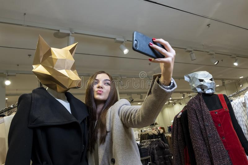 Een mooi meisje in een opslag met kleren neemt beelden van zich op de telefoon naast ledenpoppen met een dierlijk hoofd stock foto's