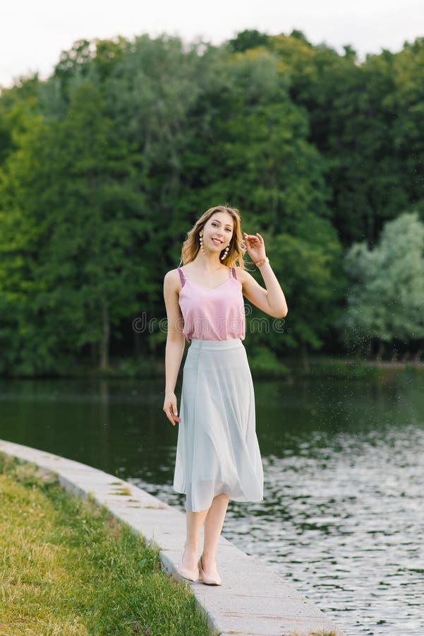 Een mooi meisje in roze en blauwe kleren loopt langs de kust van een meer of rivier in een stadspark stock foto
