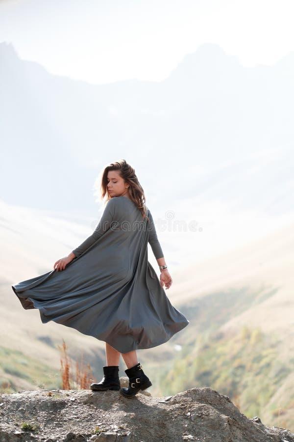 Een mooi meisje in een vliegende kleding bevindt zich door een klip in de bergen stock foto