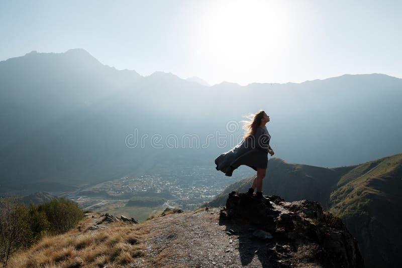 Een mooi meisje in een vliegende kleding bevindt zich op een klip overziend de bergen stock foto