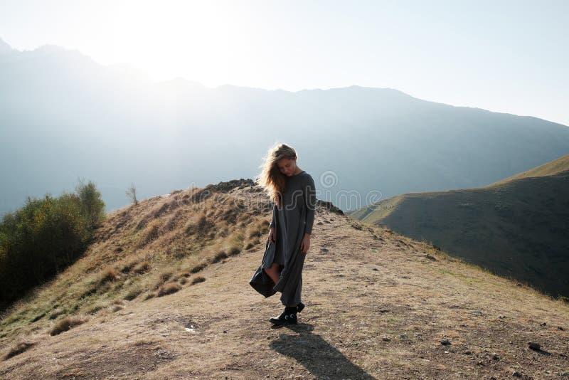 Een mooi meisje in een vliegende kleding bevindt zich op een klip overziend de bergen royalty-vrije stock foto