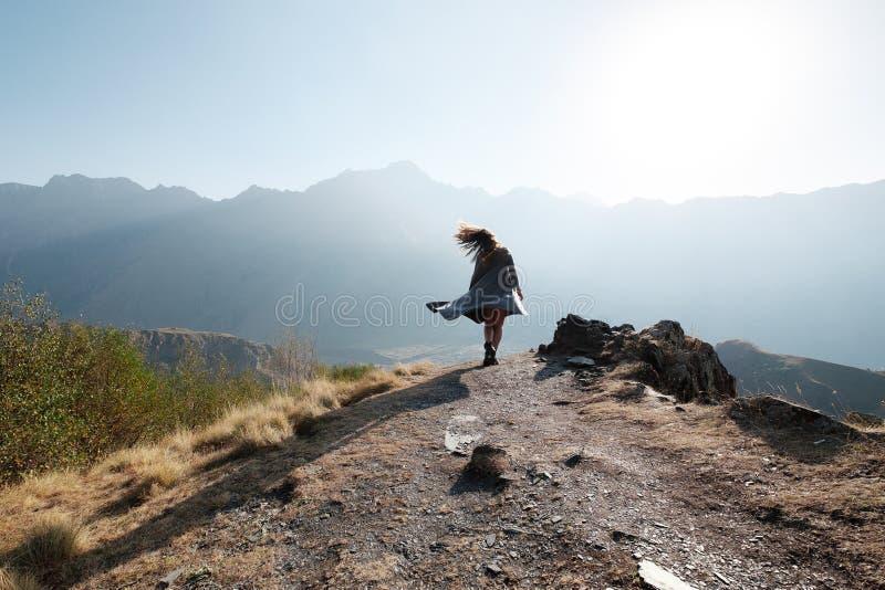 Een mooi meisje in een vliegende kleding bevindt zich op een klip overziend de bergen stock fotografie