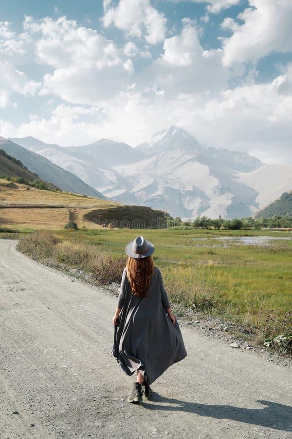 Een mooi meisje in een vliegende kleding en een hoed gaat langs de weg naar de bergen stock fotografie