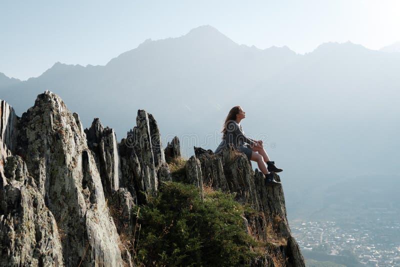 Een mooi meisje in een vliegende kleding zit op een klip overziend de bergen stock foto
