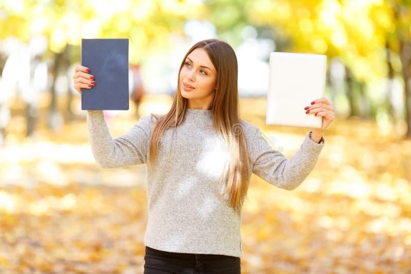 Een mooi meisje in een witte sweater houdt een boek en een tablet op de achtergrond van de herfstpark royalty-vrije stock foto