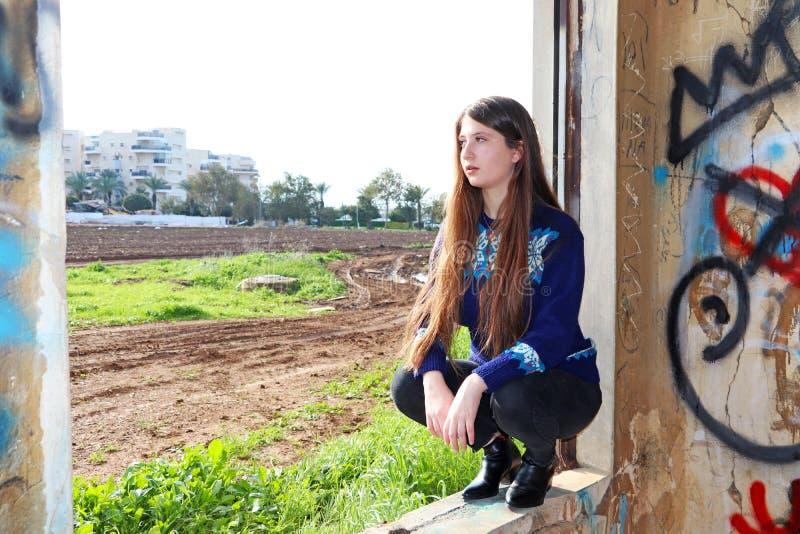 Een mooi meisje zit op een vensterbank stock foto's