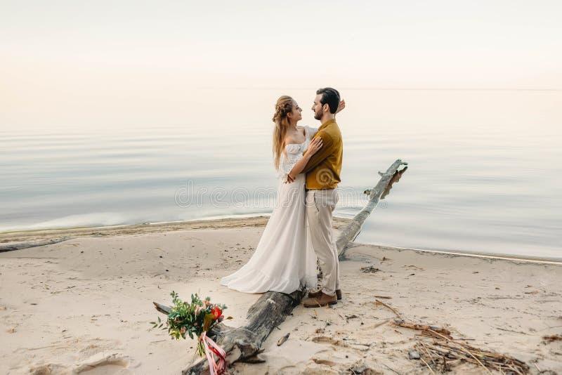 Een mooi paar omhelst op de overzeese achtergrond Ogenblik vóór de kus Romantische datum op het strand Huwelijk royalty-vrije stock fotografie