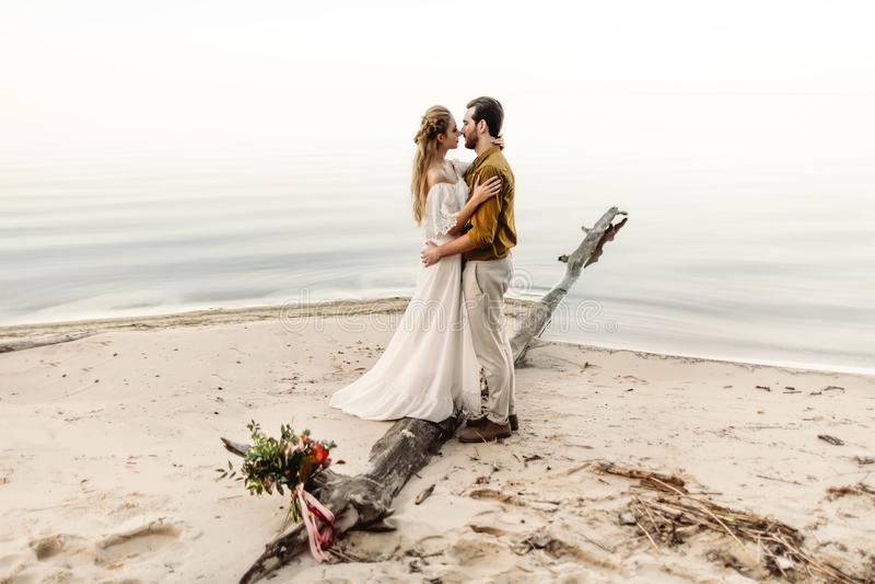 Een mooi paar omhelst op de overzeese achtergrond Ogenblik vóór de kus Romantische datum op het strand Huwelijk royalty-vrije stock foto's