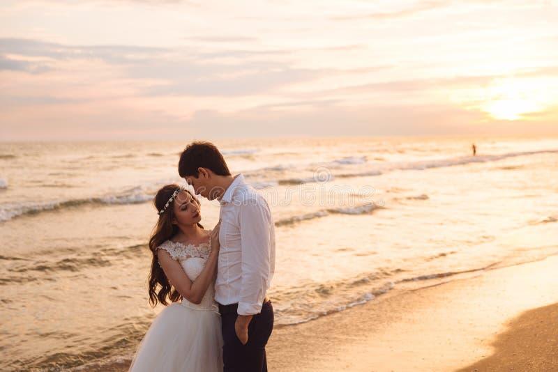 Een mooi paar van jonggehuwden, de bruid en de bruidegom die op het strand lopen Schitterende zonsondergang en hemel Huwelijkskle stock afbeeldingen