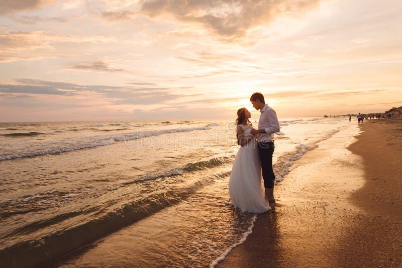 Een mooi paar van jonggehuwden, de bruid en de bruidegom die op het strand lopen Schitterende zonsondergang en hemel Huwelijkskle royalty-vrije stock fotografie