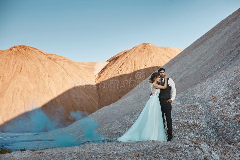 Een mooi paar van minnaars bij een witte zoute woestijn, een jonge vrouw met een huwelijkskapsel in een modieuze kleding en royalty-vrije stock afbeelding
