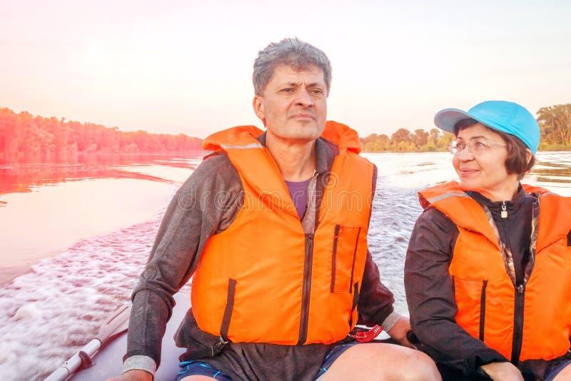 Een mooi rijp paar loopt op een motorboot om op een hete de zomerdag te komen stock foto