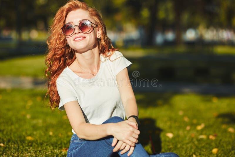 Een mooi roodharig die meisje, door de stralen van de zon wordt verwarmd, zit op een gazon en stelt voor de camera Het meisje dra royalty-vrije stock afbeeldingen