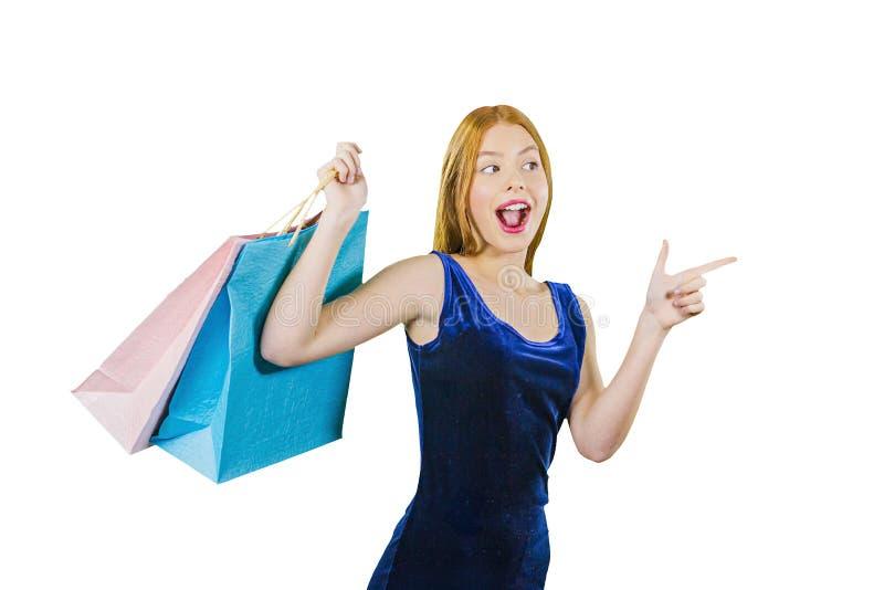 Een mooi roodharig meisje in een blauwe fluweelkleding met zakken over haar schouder toont met haar wijsvinger aan de kant royalty-vrije stock fotografie