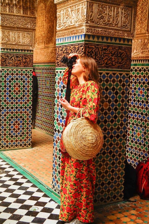 Een mooi Russisch meisje in een heldere lange kleding in het paleis van Fes neemt beelden stock afbeelding