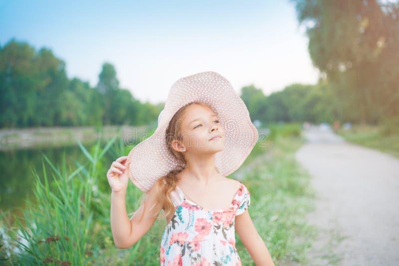 Een mooi schoolmeisje in een roze hoed in de stralen van de zonsondergang op een de zomeravond op aard royalty-vrije stock afbeeldingen