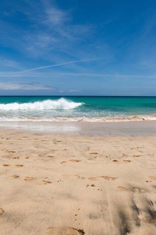 Een mooi strand met turkoois water en een blauwe hemel stock foto's