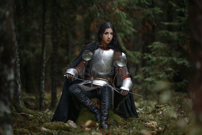 Een mooi strijdersmeisje met een zwaard die chainmail en pantser in een geheimzinnig bos dragen stock fotografie