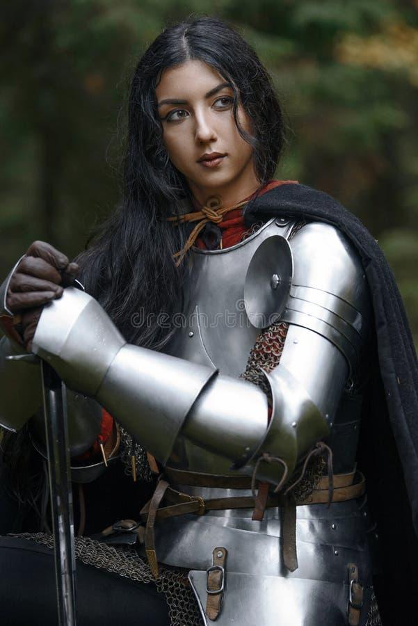 Een mooi strijdersmeisje met een zwaard die chainmail en pantser in een geheimzinnig bos dragen stock afbeelding