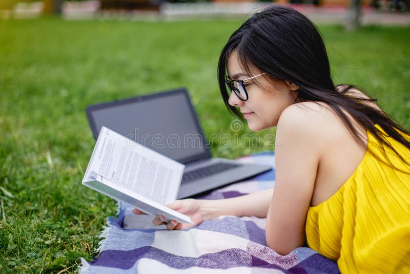 Een mooi studentenmeisje las boeken en laptop computer op het groene gras in het park in de zomertijd royalty-vrije stock fotografie