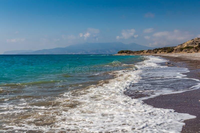 Een mooi verlaten zand en kiezelsteenstrand met schuimende golven surft en bergen en een blauwe hemel met witte wolken stock fotografie