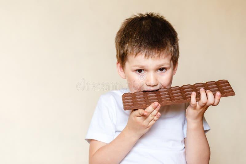 Een mooi vijf-jaar-oud Kaukasisch kind in een witte t-shirt bijt een grote melkchocola royalty-vrije stock fotografie