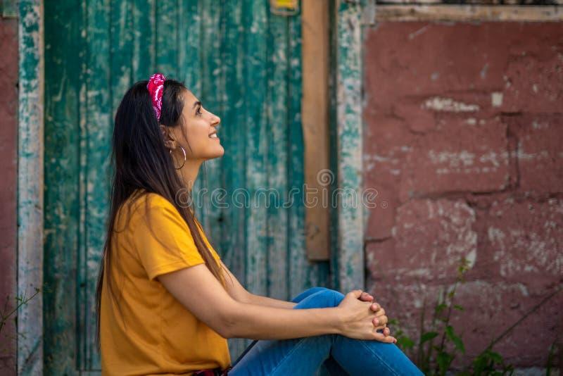 Een mooi vrouwenbrunette kleedde zich in modieuze jeans en een gele T-shirt stock foto's