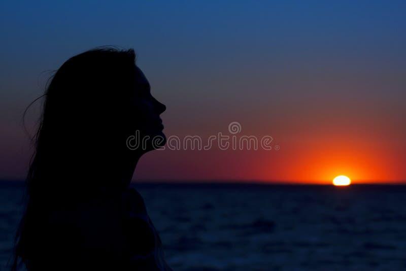 Een mooi vrouwenprofiel tegen de zonsondergang stock foto's