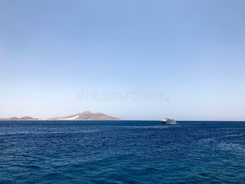 Een mooi zeegezicht die het blauwe zoute overzees, de gele zandige verre steenbergen op de tropische kusttoevlucht en de schepen  stock afbeeldingen