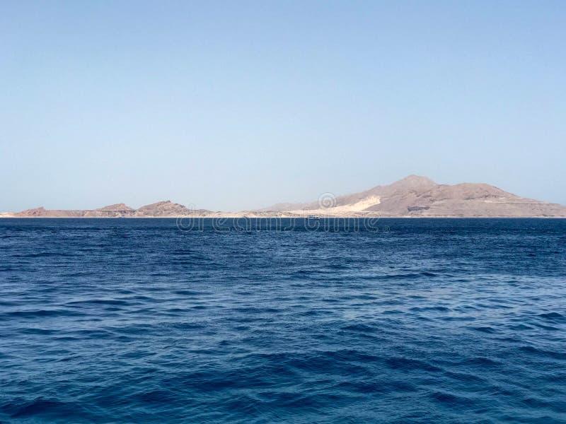 Een mooi zeegezicht die het blauwe zoute overzees, de gele zandige verre steenbergen op de tropische kusttoevlucht overzien royalty-vrije stock fotografie