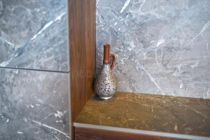 Een mooie antieke kruik, een vaas bevindt zich in de hoek van de ruimte op een marmeren lijst royalty-vrije stock fotografie