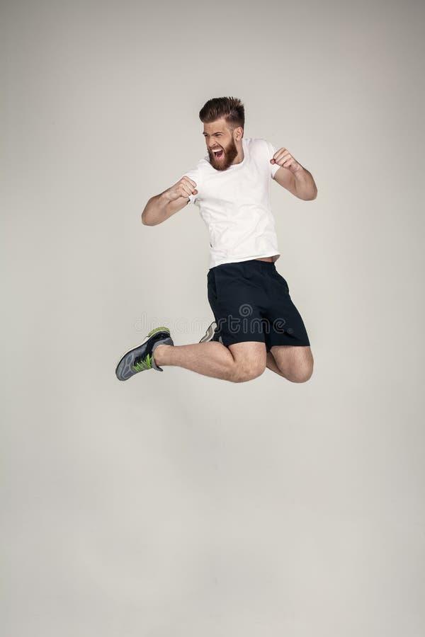 Een mooie atleet met een baard sprong op de heuvel in de studio het dragen van tennisschoenen en een witte T-shirt tegenover de w stock fotografie
